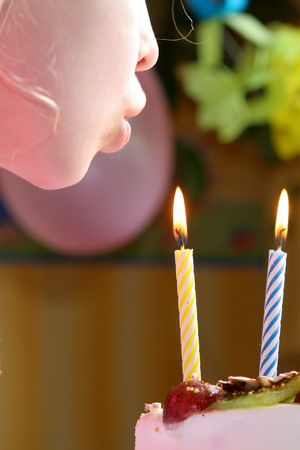 girl blowing: Young girl blowing birthday candles