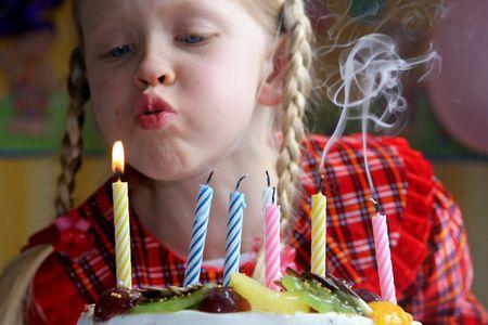 gateau bougies: Petite fille soufflant des bougies d'anniversaire
