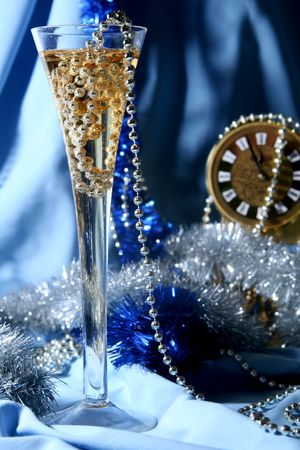 new year eve beads: Glass of champagne on a silver-blue background
