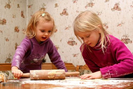christmas baker's: Children rolling out dough for christmas cookies