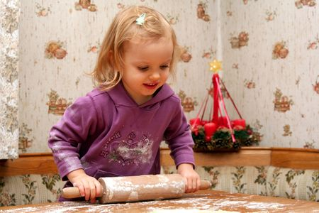 Children rolling out dough for christmas cookies photo