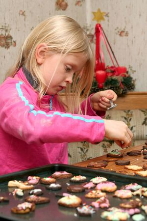 Children decorating christmas cookies with colorful ice photo