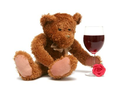 Teddy bear with glass of wine on a white background photo