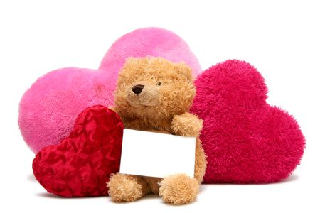 Teddy bear with soft hearts on a white background photo