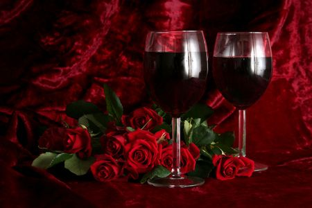 amore: Glass of wine on a dark red background