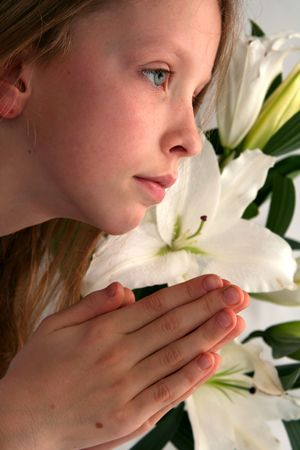 Little girl praying on the easter lilies background Stock Photo