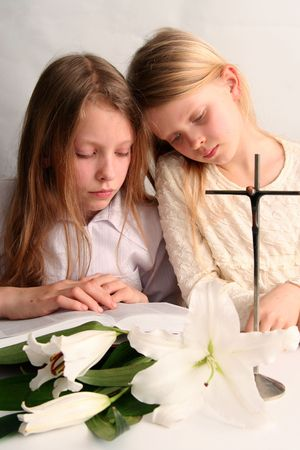 Two sister reading holy bible together and easter lilies lying on the table.  photo