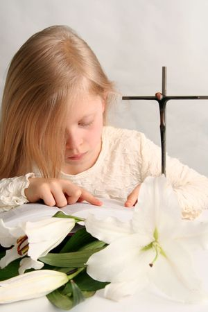 Little girl  reading holy bible  and easter lilies lying on the table.