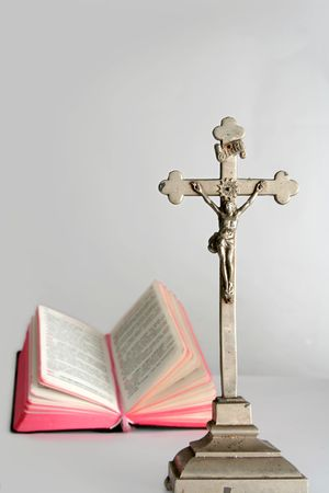 Opened prayerbook and old cross  on a white background