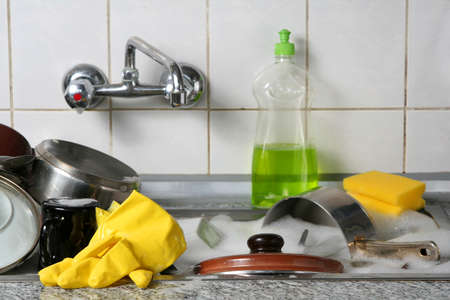 messy kitchen: Pile of dirty dishes in the metal sink