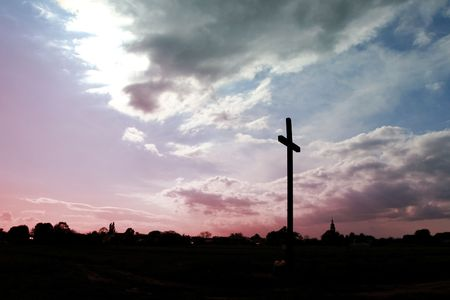 worshipper: Wooden  catholic cross   on a sky background