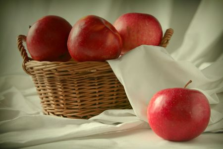 pome: Red fresh apples in basket on a white fabric  background