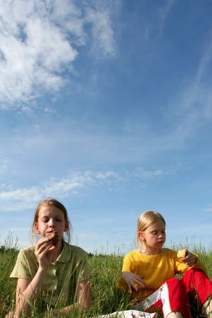 Children sitting in the grass on a blue sky background Stock Photo - 1052715