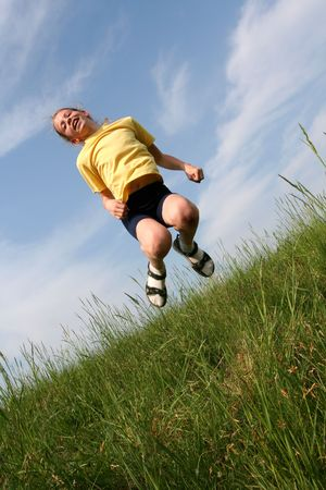 Young girl jumping in grass on a blue sky background. Motion blur Stock Photo - 1067781