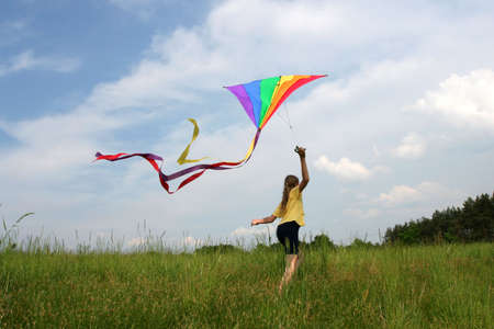 flying a kite: Children flying rainbow kite in the meadow on a blue sky background Stock Photo