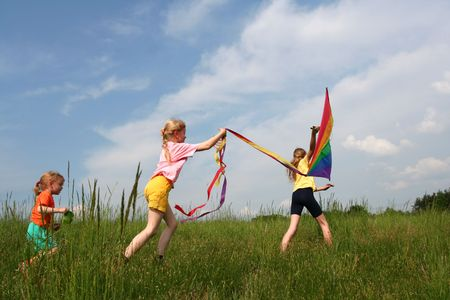 Children flying rainbow kite in the meadow on a blue sky background photo