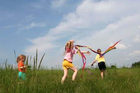 exaltation: Children flying rainbow kite in the meadow on a blue sky background Stock Photo