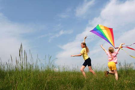 凧: 青空をバックに牧草地の虹凧をフライング子供