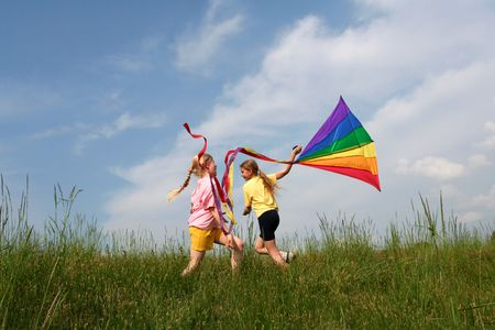 kite: Children flying rainbow kite in the meadow on a blue sky background Stock Photo