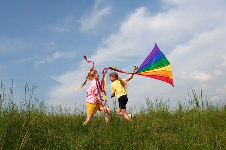 papalote: Los ni�os de vuelo arco iris cometa en el prado en un cielo azul de fondo