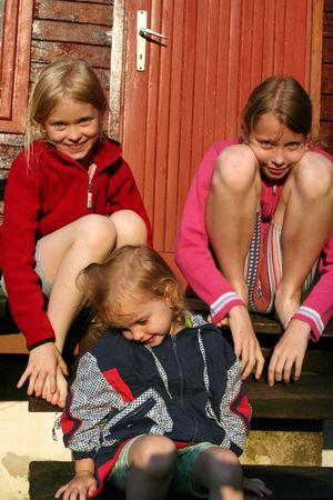 barefooted: Barefooted girls sitting on old wooden stairs