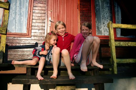 Barefooted girls sitting on old wooden stairs