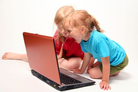 lear: Two little girls playing on laptop on a light background