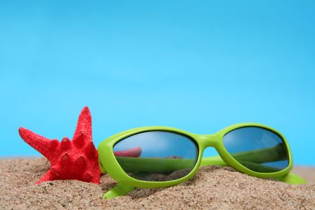 Green sunglasses and sand on a blue background photo