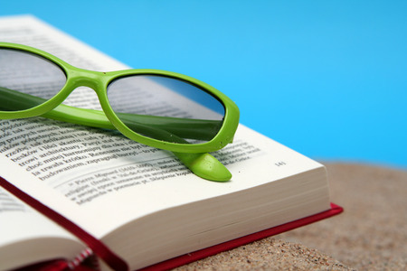 beach wear: Opened book on a sand with green sunglasses