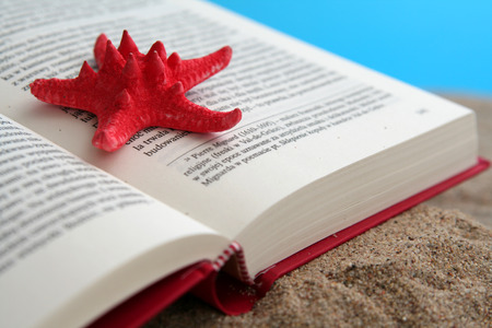 Opened book on a sand with red starfish photo