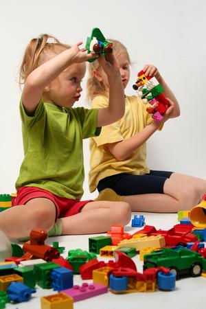 A pequeños niños jugando con bloques de colores cubo  Foto de archivo - 1478912