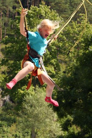 puenting: Peque�a muchacha rubia en mini saltar del amortiguador auxiliar Foto de archivo