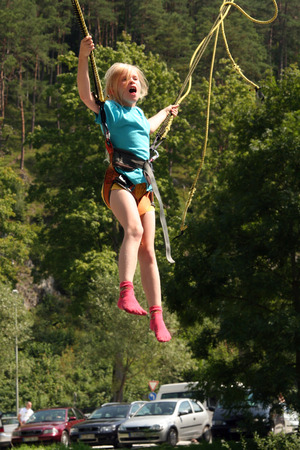 puenting: Poco chica rubia en un mini bungee-jumping
