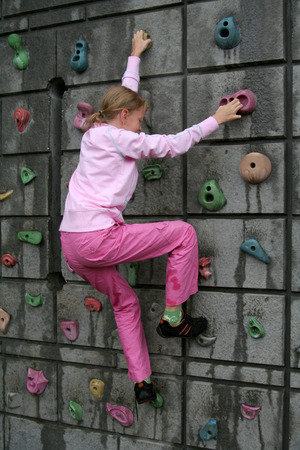 Blond girl in pink climbing a garden rock wall