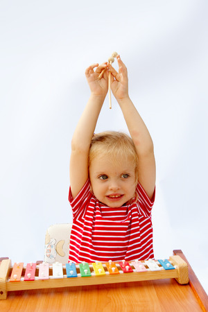 red tshirt: Little girl wearing striped red t-shirt playing the rainbow xylophone Stock Photo