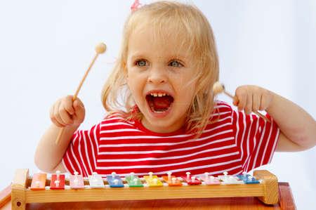 xilofono: Peque�a muchacha que usa la camiseta roja rayada que toca el xil�fono del arco iris Foto de archivo