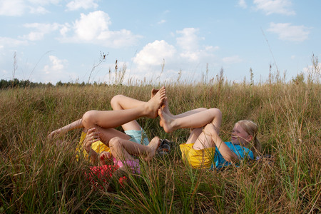 exaltation: Girls wearing colorful t-shirts playing on a meadow
