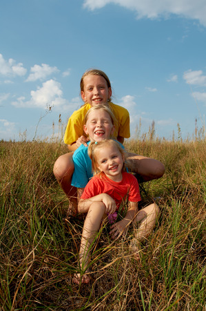 Girls wearing colorful t-shirts playing on a meadow Stock Photo - 1674846