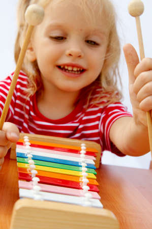 infant girl: Little girl wearing striped red t-shirt playing the rainbow xylophone Stock Photo