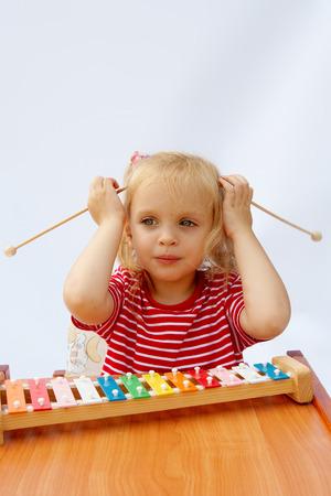 xylophone: Peque�a muchacha que usa la camiseta roja rayada que toca el xil�fono del arco iris Foto de archivo
