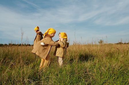 Children wearing yellow caps  playing on autumnal meadow Stock Photo - 1769671