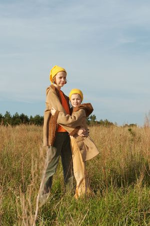 Children wearing yellow caps  playing on autumnal meadow Stock Photo - 1828096