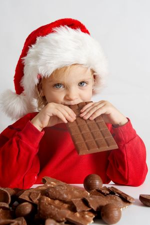 Little girl wearing red Santa hat eating chocolate