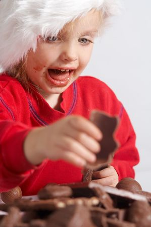 Little girl wearing red Santa hat eating chocolate photo