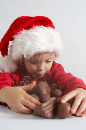Little girl wearing red Santa hat eating chocolate photo