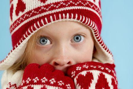 Little blond girl wearing woolen cap, scarf and gloves photo