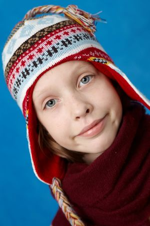 Young girl wearing woolen cap, scarf and gloves on blue  photo
