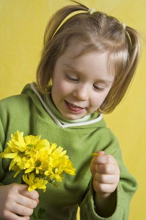 Little girl in green and yellow daisies photo
