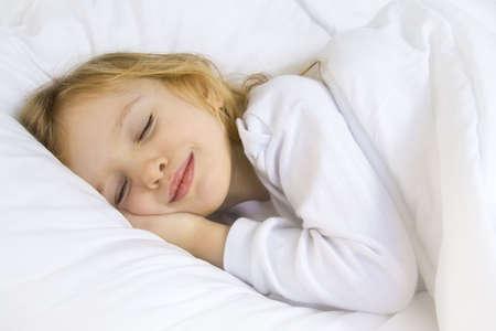 ni�o durmiendo: Poco chica rubia llevaba blusa blanca en blanco bedchlothes Foto de archivo
