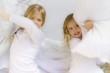 Little blond girl wearing white blouse in white bedchlothes Stock Photo